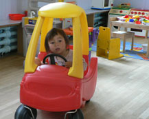 girl driving in a toy car
